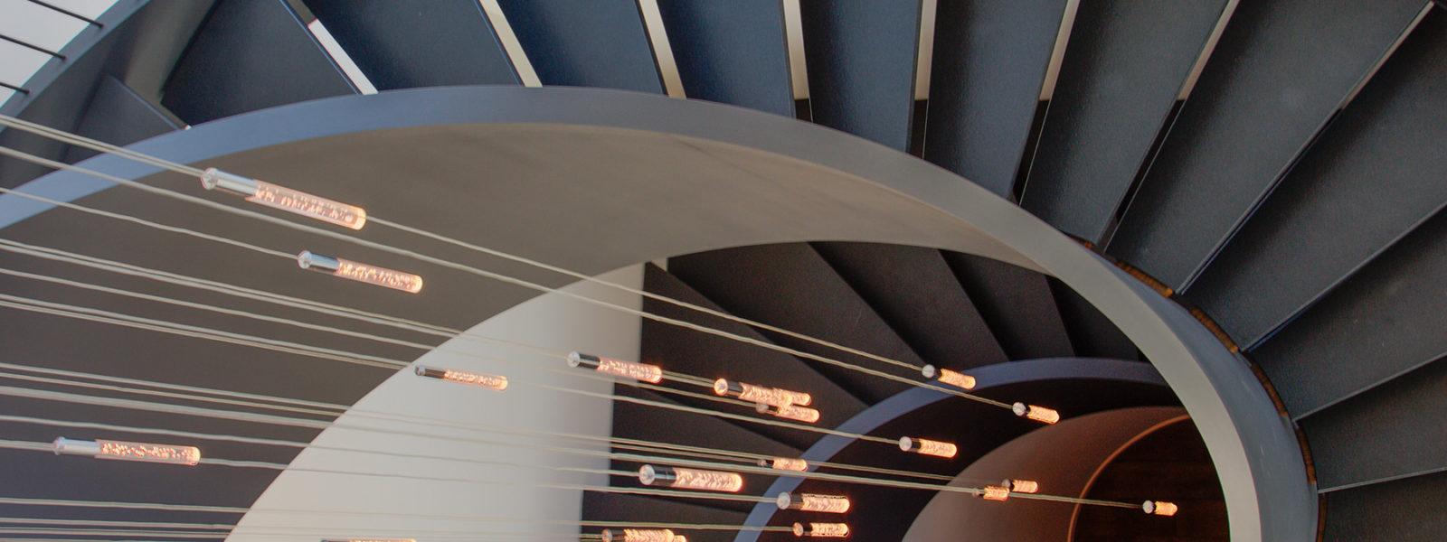 Modern Stone, Wood, and Metal Curved Stairway by Arcways Custom Stairs