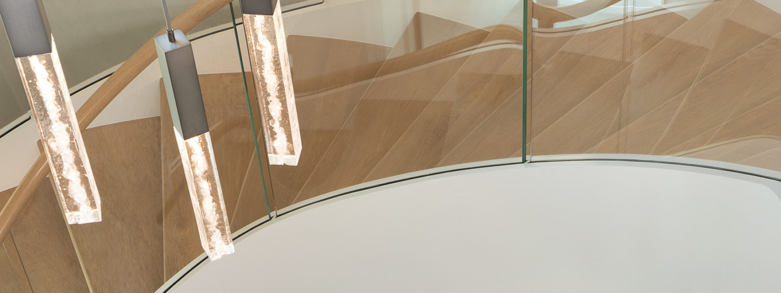 Modern Curved Spiral Stairway With Glass Balustrade and Integrated Lighting By Arcways